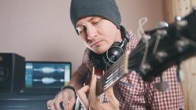 Młody męski muzyk komponuje ścieżkę dźwiękowa bawić się gitarę i nagrywa używać komputer, hełmofony i klawiaturę, obrazy royalty free
