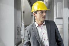 Młody męski nadzorca jest ubranym ciężkiego kapelusz patrzeje daleko od w przemysle Obrazy Royalty Free