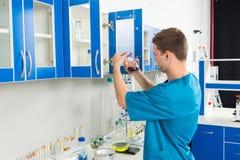Młody męski naukowiec w mundurze jest przyglądającym butelką z chemi obrazy royalty free
