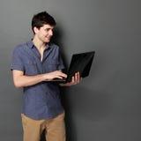 Młody męski ono uśmiecha się używa laptop Zdjęcie Royalty Free