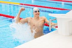 Młody męski pływaczki odświętności zwycięstwo w pływackim basenie Fotografia Stock