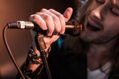 Młody męski piosenkarz z mikrofonem na scenie Fotografia Royalty Free