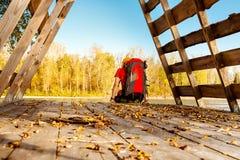 Młody męski podróżować, odpoczywający na banka halnym rzecznym obsiadaniu w budzie gałąź, z turystycznym plecakiem podczas gdy Zdjęcie Royalty Free