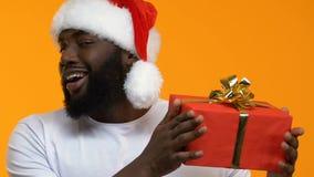 Młody męski pokazuje prezenta pudełko i mrugać kamera, sezonowy rabat, świętowanie zbiory