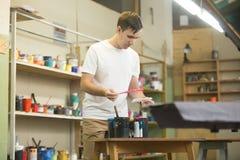 Młody męski pracownik wybiera odpowiednich atramenty Fotografia Stock