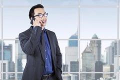 Młody męski przedsiębiorca opowiada na telefonie komórkowym Obrazy Stock