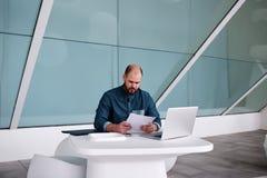 Młody męski przedsiębiorcy czytania papieru raport podczas gdy siedzący przed otwartą książką w nowożytnym biurowym wnętrzu, Obrazy Royalty Free
