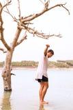 Młody męski równoważenie na skale w zalewającym jeziorze Obrazy Stock