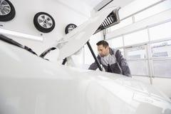 Młody męski samochodu mechanik egzamininuje samochodowego silnika w remontowym sklepie Zdjęcie Stock