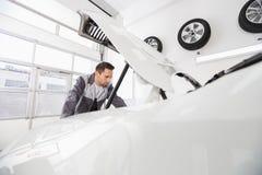 Młody męski samochodu mechanik egzamininuje samochodowego silnika w remontowym sklepie Obraz Stock