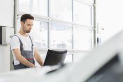 Młody męski samochodu mechanik używa komputer w remontowym sklepie Zdjęcie Stock