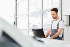 Młody męski samochodu mechanik używa komputer w remontowym sklepie obrazy stock
