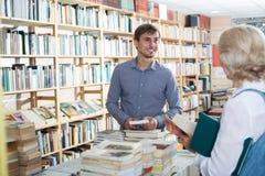 Młody męski sprzedawca w książkowym sklepie Obraz Stock