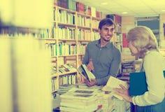 Młody męski sprzedawca w książkowym sklepie Zdjęcia Stock