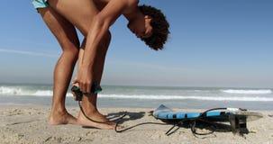 Młody męski surfingowiec wiąże surfboard smycz 4k zbiory wideo