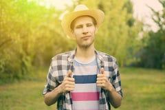 Młody męski szczęśliwy uśmiechnięty rolnik w kapeluszu i przypadkowej koszula w wsi naturalnym gospodarstwie rolnym a zdjęcie stock