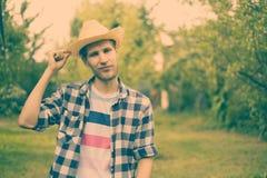 Młody męski szczęśliwy uśmiechnięty rolnik w kapeluszu i przypadkowej koszula w wsi naturalnym gospodarstwie rolnym a obrazy stock