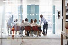Młody męski szef stoi opierać na stole przy biznesowym spotkaniem zdjęcia stock
