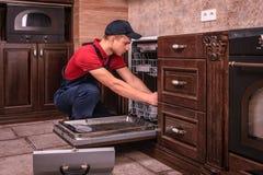 Młody Męski technika naprawiania zmywarki do naczyń W kuchni fotografia royalty free