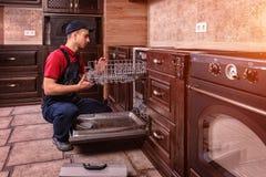 Młody Męski technika naprawiania zmywarki do naczyń W kuchni zdjęcie royalty free