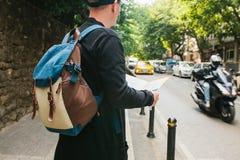 Młody męski turysta z plecakiem w dużym mieście ogląda mapę journeyer Zwiedzać Podróż zdjęcie royalty free