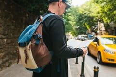 Młody męski turysta z plecakiem w dużym mieście ogląda mapę journeyer Zwiedzać Podróż zdjęcia stock