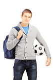 Młody męski uczeń trzyma futbol z szkolną torbą Zdjęcia Royalty Free