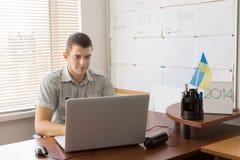 Młody Męski urzędnik Ruchliwie z Jego laptopem Fotografia Stock