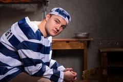 Młody męski więzień jest ubranym więzienie munduru spojrzenia przy kamerą w Obrazy Royalty Free
