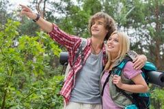 Młody męski wycieczkowicz pokazuje coś kobieta w lesie Fotografia Royalty Free