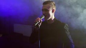 Młody męski wykonawcy śpiew w ciemnym dymiącym pokoju zbiory