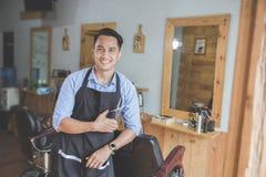 Młody męski zakładu fryzjerskiego właściciela ono uśmiecha się Zdjęcie Royalty Free