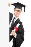 Młody męskiego ucznia mienia dyplom i pozycja za pustą niecką Obrazy Royalty Free
