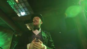 Młody magik w kostiumu i czarnym kapeluszu wykonuje na scenie zbiory wideo