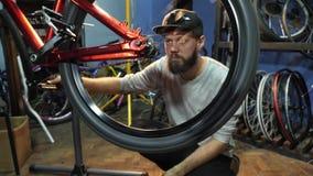 Młody mahanic naprawianie rowerowy toczy wewnątrz jej remontowego warsztat zbiory