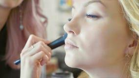 Młody makeup artysta stosuje concealer na wzorcowej ` s twarzy fotografia stock