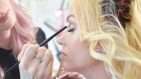 Młody makeup artysta stosuje kosmetyki na wzorcowym ` s ono przygląda się fotografia stock