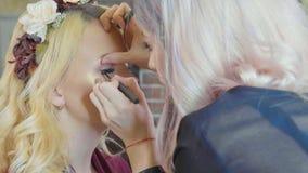 Młody makeup artysta stosuje kosmetyki na wzorcowym ` s ono przygląda się zdjęcie royalty free
