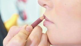 Młody makeup artysta stosuje pomadkę na wzorcowych ` s wargach zdjęcie royalty free