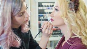 Młody makeup artysta stosuje pomadkę na wzorcowych ` s wargach zdjęcia royalty free