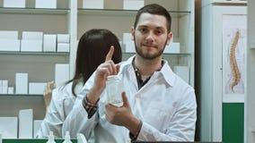 Młody malepharmacist trzyma białą pustą butelkę pigułki, promuje medycynę, podczas gdy jego kolegi działanie Fotografia Stock