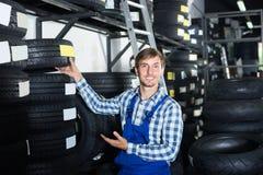 Młody mechanika mężczyzna pracuje z samochodowymi oponami w warsztacie zdjęcie stock
