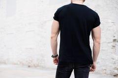 Młody mięśniowy brodaty mężczyzna jest ubranym czarnego tshirt i cajgi pozuje w centrum nowożytny miasto Pusta betonowa ściana na Obrazy Stock