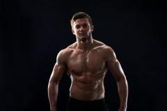 Młody mięśniowy dysponowany sportowa pozować bez koszuli na czarnym backgroun Obrazy Royalty Free