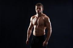Młody mięśniowy dysponowany sportowa pozować bez koszuli na czarnym backgroun obraz stock