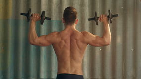 Młody mięśniowy mężczyzna ćwiczy z dumbbells zdjęcie wideo