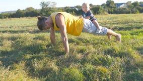 Młody mięśniowy ojciec podnosi z jego małym synem na jego z powrotem robić pcha Sportowy mężczyzna robi Ups przy zieloną trawą z Obrazy Royalty Free
