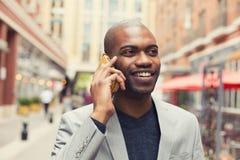 Młody miastowy fachowy uśmiechnięty mężczyzna używa mądrze telefon Zdjęcia Royalty Free