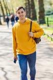 Młody miastowy mężczyzna używa smartphone odprowadzenie w ulicie w miastowym parku w Londyn fotografia royalty free