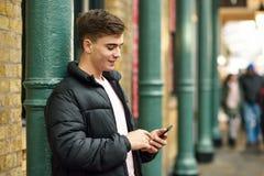 Młody miastowy mężczyzna używa smartphone w miastowym tle zdjęcia royalty free
